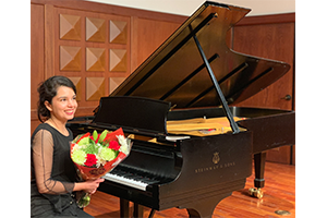 Leili holding flowers in front of a piano.