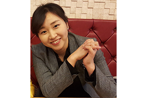 Smiling Ahyoung sitting on a red leather sofa.