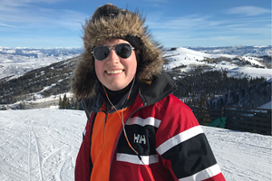 Johnathan smiling in front of snowy mountains.