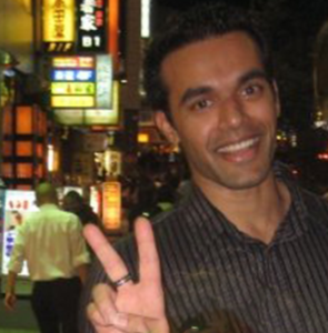 Celso making a peace sign on the night streets of Tokyo.