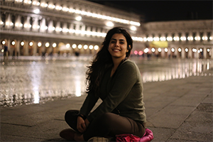 Zahra sitting in a flooded San Marco Square.