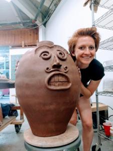 Aisha crouching next to a big ceramic pot she made.
