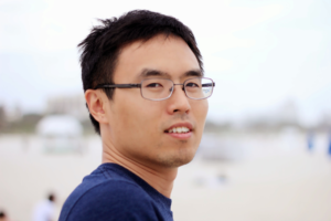 Young Asian man in front of blurred background.