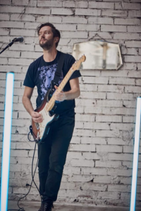Young man playing bass guitar in front of a white distressed brick background.